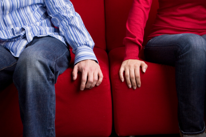 couple on couch with hands close but not touching
